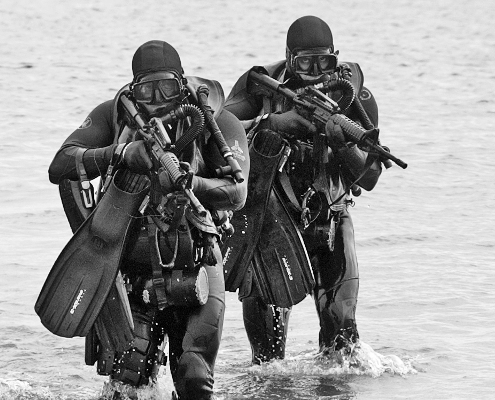 navy seals in tactical gear running out of water